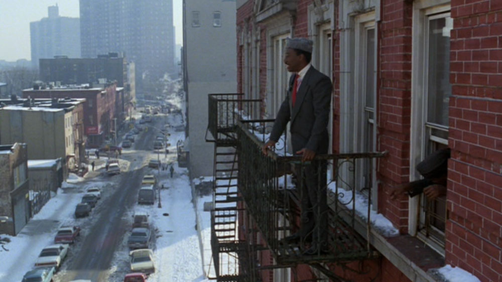 Eddie Murphy standing on a fire escape.